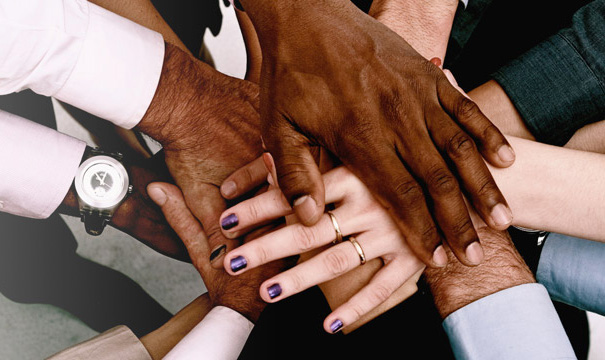 multi-ethnic stack of hands reaching inward in a show of solidarity.